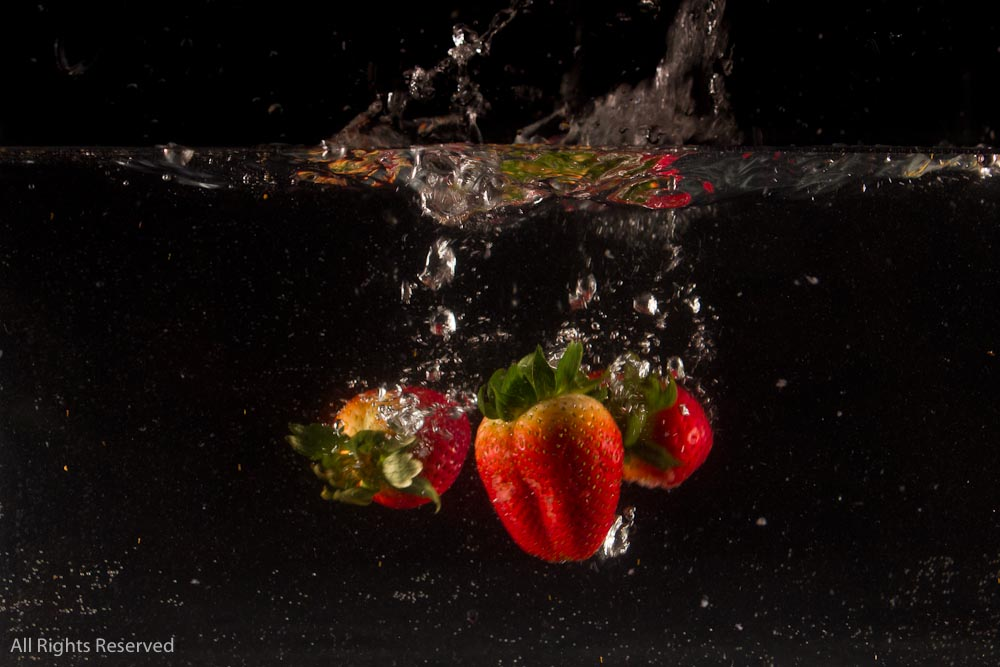 Strawberry dropping into water